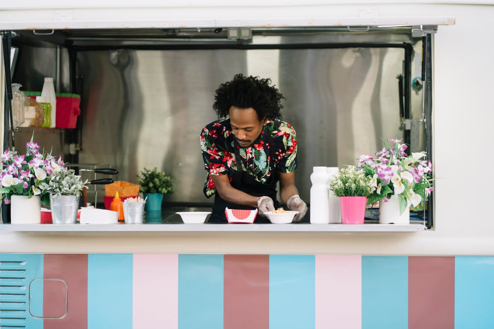 Young man preparing food in his food truck business