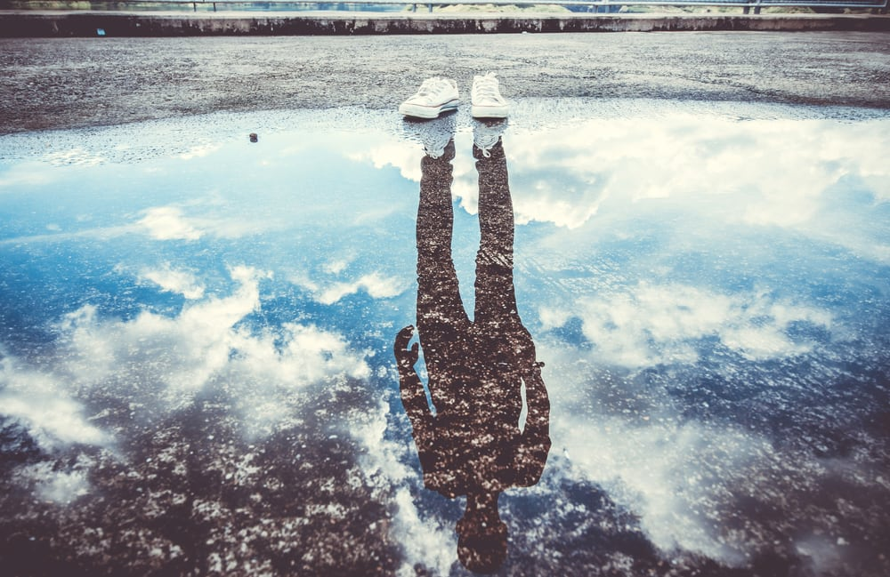 A pair of shoes at the edge of water with a reflection of a person.