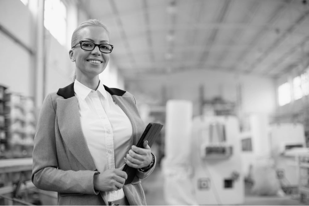 Businesswoman in factory with tablet device.