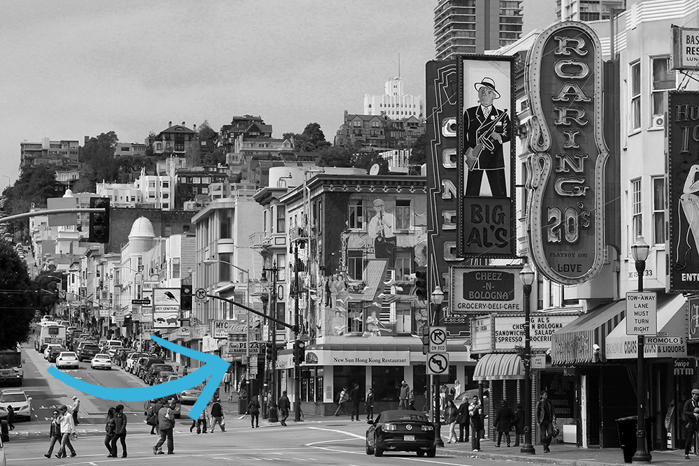 A photo looking up Broadway Street in San Francisco, with iconic neon signs in the foreground and an arrow pointing to the location of Sam's restaurant halfway up the block.